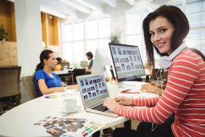 Graphic designer looking at camera while colleague working in background in the office