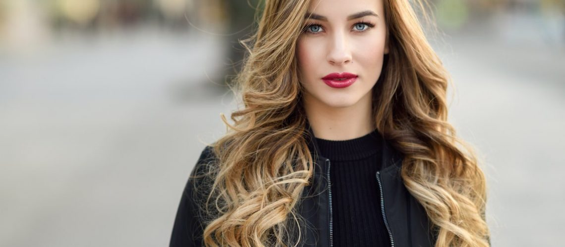 Close-up portrait of young blonde girl with beautiful blue eyes wearing black jacket outdoors. Pretty russian female with long wavy hair hairstyle. Woman in urban background.